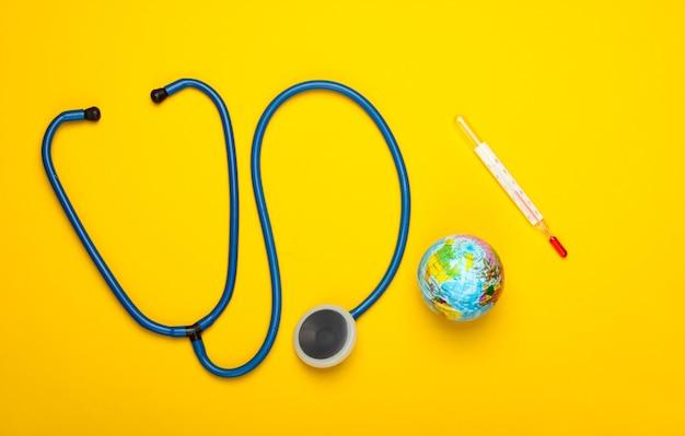 Il riscaldamento globale ancora in vita. globo e termometro, stetoscopio sulla parete gialla questioni climatiche globali. trattamento del pianeta terra. concetto di eco. vista dall'alto