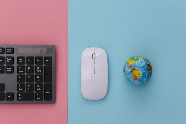 Web globale. tastiera per pc con mouse per pc, globo su pastello blu rosa