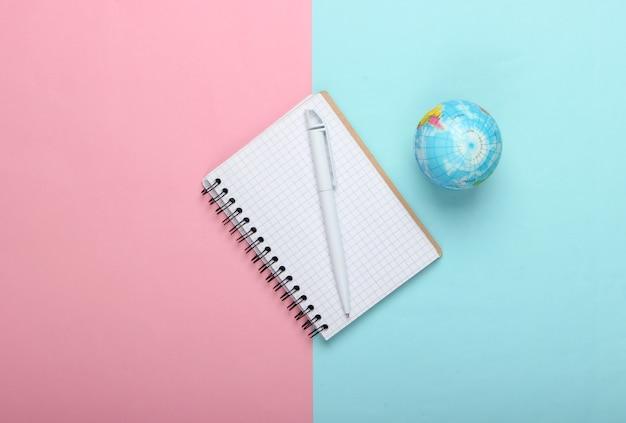Globo e taccuino su sfondo rosa pastello blu. vista dall'alto. minimalismo. concetto di educazione, geografia