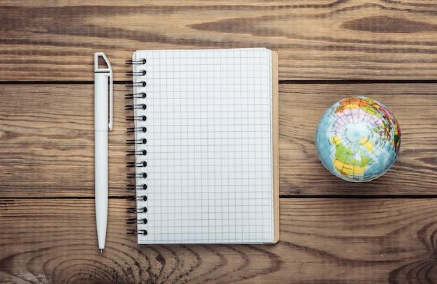 Globo e taccuino sulla tavola di legno. vista dall'alto. minimalismo. concetto di educazione, geografia