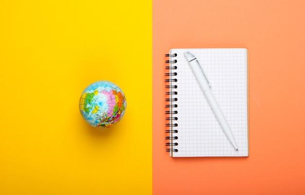 Globo e taccuino su sfondo giallo arancio. vista dall'alto. minimalismo. concetto di educazione, geografia