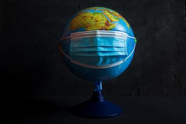 Globo in una mascherina medica protettiva. il coronavirus attacca il pianeta.
