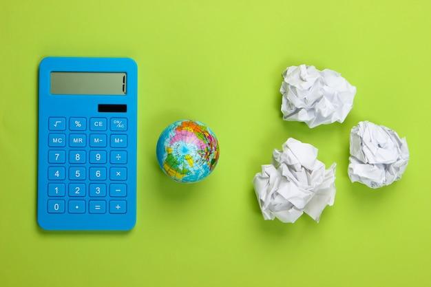 Globo con palline di carta stropicciata, calcolatrice sul verde. salva il pianeta. arte concettuale.