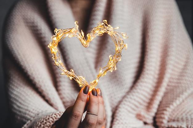 Cuore luminoso nelle mani di una donna. buon san valentino. plaid, comfort, inverno, cuore inghirlandato nelle mani di una donna. buon san valentino