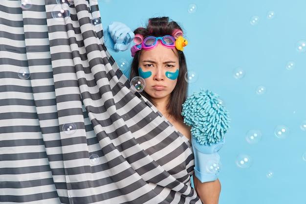 Una donna asiatica cupa e insoddisfatta applica prodotti per la cura della pelle che si nasconde dietro la tenda della doccia a righe si diverte a fare la doccia indossa guanti e tiene una spugna