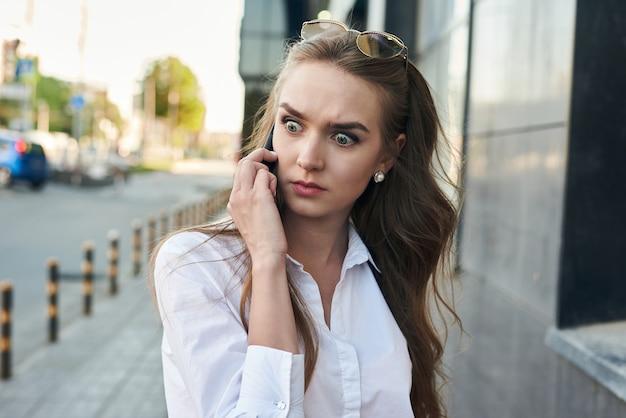 Ragazza cupa sta parlando su fina. la ragazza con il telefono ha fretta.