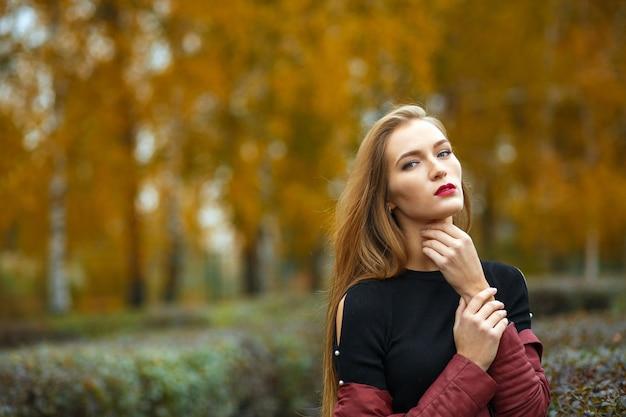 Gloriosa donna bionda dai capelli lunghi con labbra rosse in posa nel giardino d'autunno. spazio per il testo