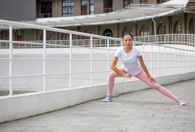 Gloriosa ragazza atletica abbronzata che indossa abbigliamento sportivo facendo stretching allenamento allo stadio. spazio per il testo