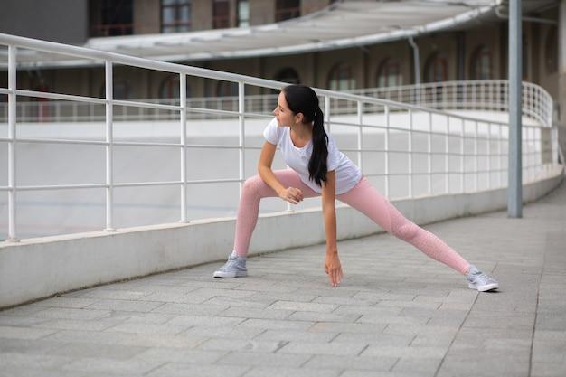 Gloriosa donna atletica abbronzata che indossa abiti sportivi facendo allenamento di stretching allo stadio. spazio per il testo