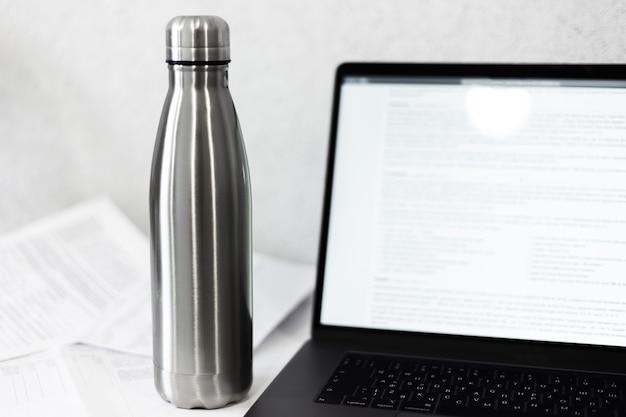 Bottiglia termica in acciaio argento lucido sulla scrivania con laptop e documenti