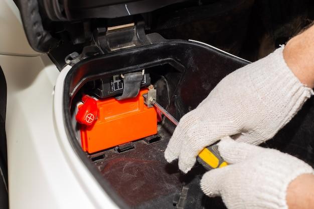 Un meccanico guantato con un cacciavite svita i terminali della batteria della motocicletta per la riparazione o