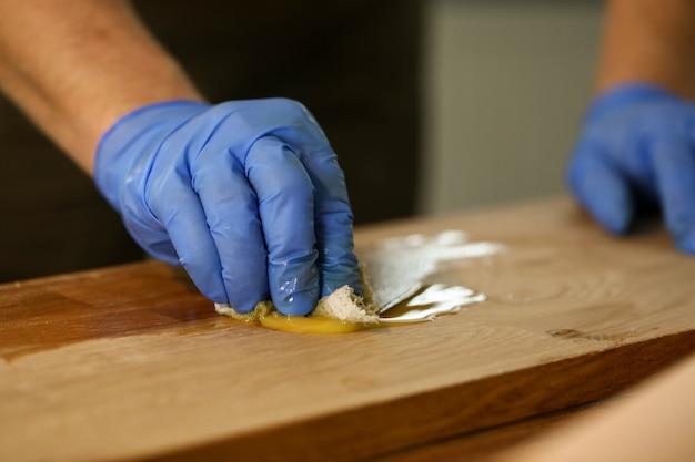 Il carpentiere con guanti fa il trattamento idrotermale del legno