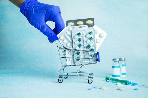 Il corriere guantato consegna un carrello con le pillole ordinate. ordinazione online in farmacia. consegna sicura e senza contatto di medicinali tramite corriere. attività farmaceutica. copia spazio.