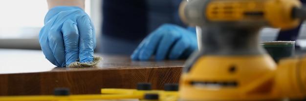 L'artigiano guantato tratta la superficie di legno con liquido protettivo