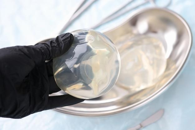 Il medico guantato tiene la protesi mammaria al silicone. concetto di chirurgia di aumento del seno