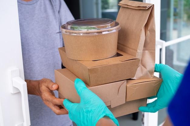 Un impiegato guantato sta inviando scatole di cibo ai clienti sulla soglia, secondo l'ordine. concetto di consegna, consegna online