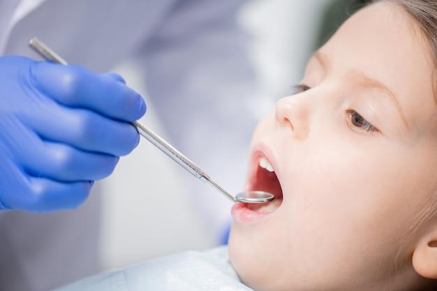 Mano guantata del dentista che esamina i denti del piccolo paziente sveglio con lo specchio dentale prima della procedura di riparazione medica