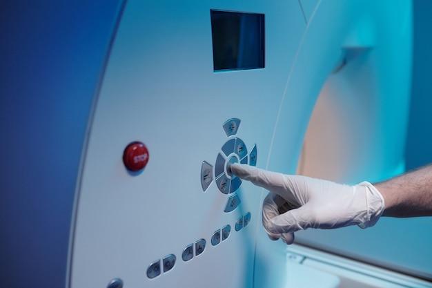 Mano guantata del medico che preme il pulsante di avvio sul pannello della macchina per la risonanza magnetica