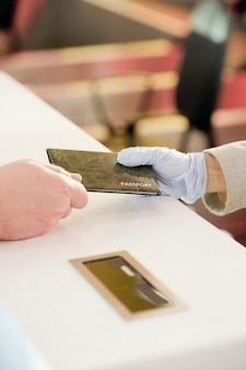 Mano guantata della receptionist donna in piedi al bancone e restituzione del passaporto del passeggero maschio dopo la registrazione prima del volo