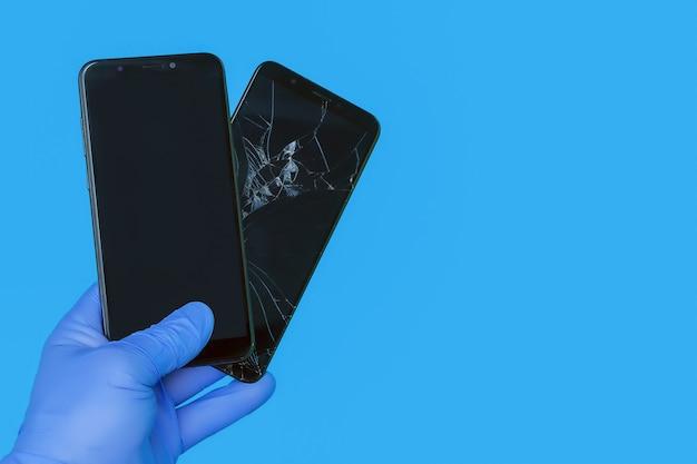 La mano guantata tiene il nuovo smartphone sostituendo un vecchio smartphone rotto con uno schermo rotto su uno sfondo blu, il concetto di un servizio di riparazione di smartphone di qualità
