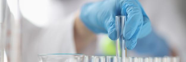 La mano guantata elimina le nuove tecniche della provetta medica nel concetto di sviluppo di farmaci
