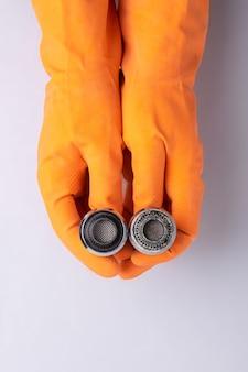 Le mani guantate tengono l'ugello del rubinetto in condizioni corrose dall'acqua e pulite.