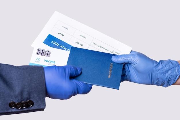 Mani guantate che porgono documenti per il viaggio aereo all'ufficiale per controllare. passaporto, biglietto, test pcr covid-19, primo piano.