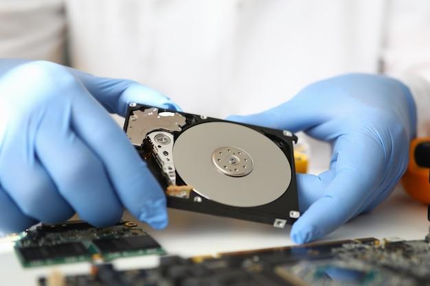 Il master guantato tiene il disco rigido lontano dal computer.