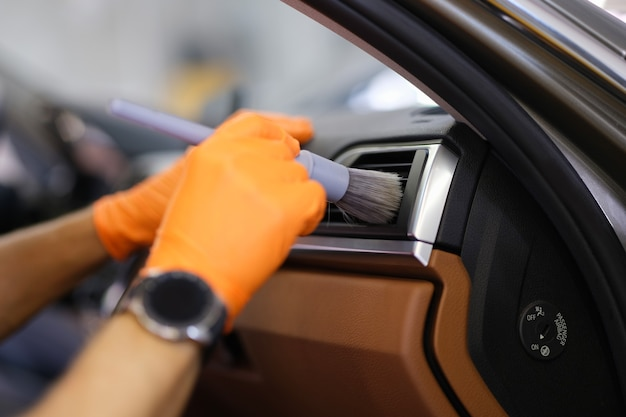 Tecnico in guanti con spazzola per pulire il sistema di ventilazione in primo piano dell'auto