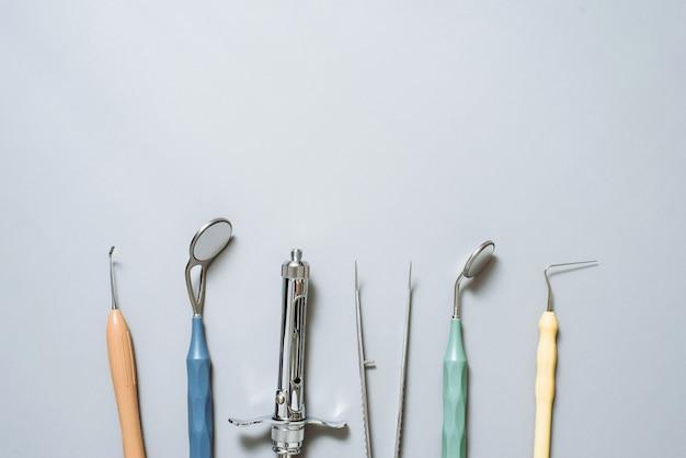 Guanti, specchio dentale, siringa per anestesia, sonde, pinzette su un blu