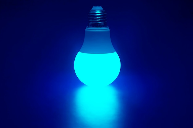 Lampada led verde brillante incandescente su un blu scuro.