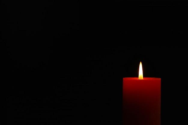 Candela incandescente su nero, spazio per il testo Foto Premium