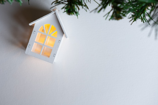 Ghirlanda di casa in legno incandescente su un albero di natale su uno sfondo bianco.