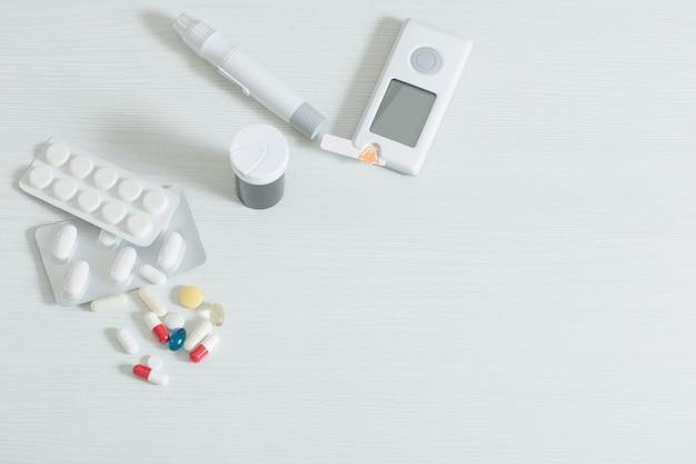 Glucometro e pillole sulla tavola di legno bianca