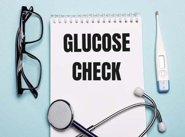 Controllo glucosio scritto su un blocco note bianco accanto a uno stetoscopio, occhiali e un termometro elettronico su una superficie azzurra