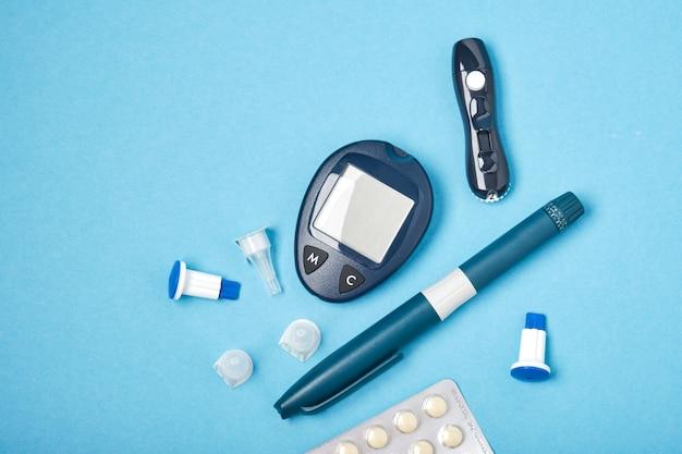 Glucometro, lancetta, siringa e pillole, aghi per iniezione, sfondo blu, copia vista dall'alto