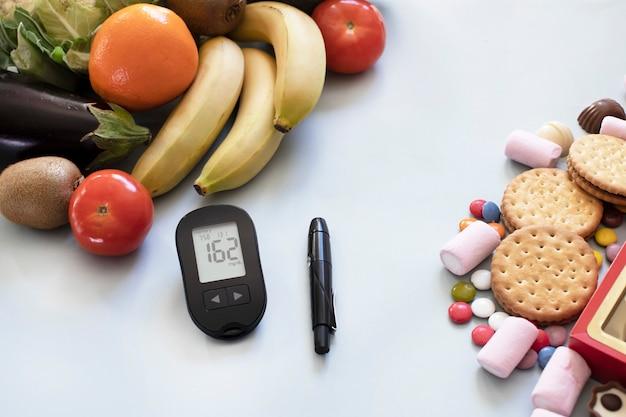 Misuratore di glucosio e cibi sani a basso indice glicemico per dieta diabetica vs cibo malsano