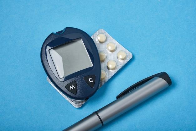 Monitor del misuratore di glucosio, penna della siringa da insulina e pillole su una vista dall'alto di sfondo blu copia spazio