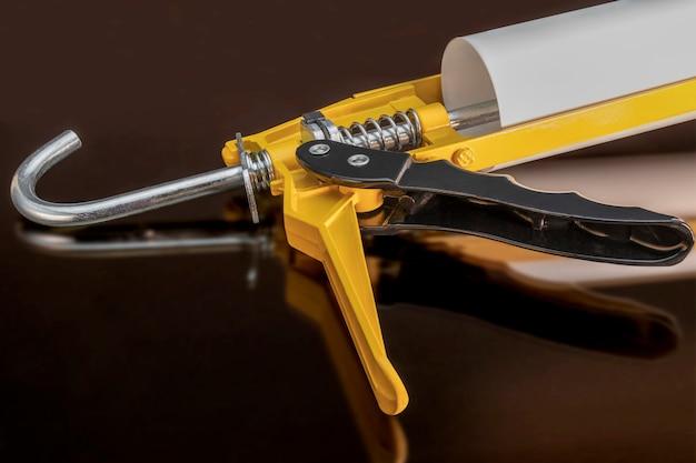 Pistola per colla e sigillante con riflessione su sfondo nero. strumento di costruzione per silicone e colla. avvicinamento.