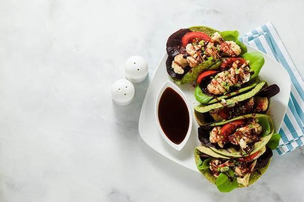Tachos verdi vegani senza glutine a base di farina di ceci con spinaci e condimenti di cavolfiore al forno