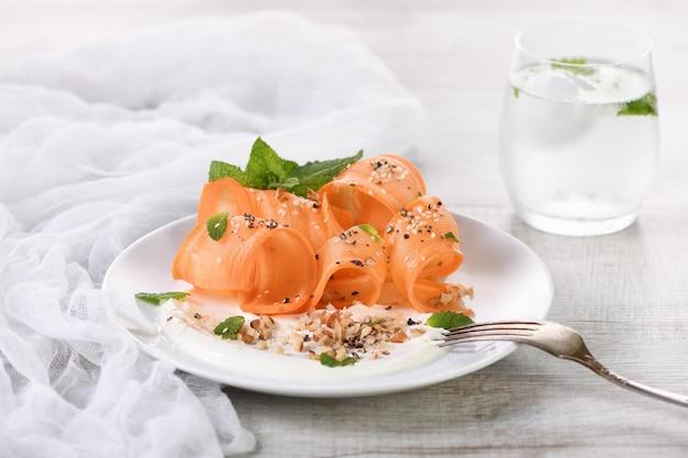 Insalata vegetariana senza glutine con carote e yogurt condita con noci tritate e spezie
