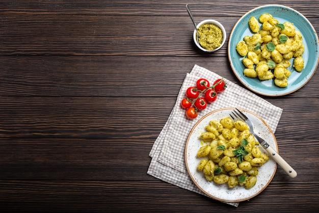 Gnocchi in piatti con salsa di pesto verde, pomodori ed erbe aromatiche su fondo di legno rustico con spazio per il testo, primo piano, vista dall'alto. piatto tradizionale della cucina italiana