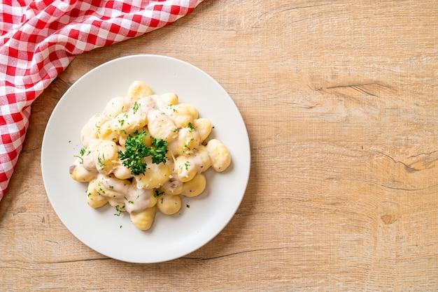 Gnocchi con salsa di crema di funghi e formaggio - stile alimentare italiano