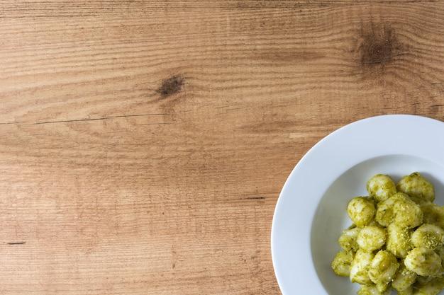 Gnocchi con la salsa di pesto in piatto sulla tavola di legno