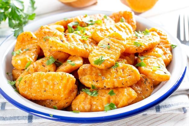 Gnocchi con una zucca sul piatto. gnocchi italiani al burro. pasto autunnale.