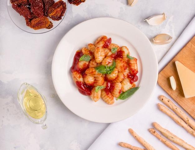 Gnocchi al sugo di pomodoro su fondo chiaro. vista dall'alto. cibo italiano