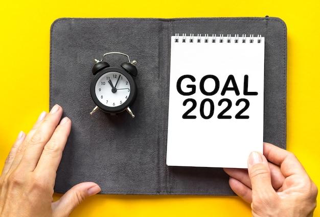 La mano da donna dell'obiettivo 2022 tiene il blocco note e una piccola sveglia su sfondo giallo