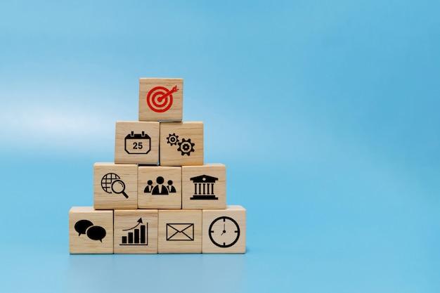 Obiettivo. icona di finanza aziendale su pila piramidale di blocchi di cubo di legno su sfondo blu con spazio di copia, marketing online, servizi bancari, investimenti, strategia aziendale, tecnologia internet e concetto finanziario