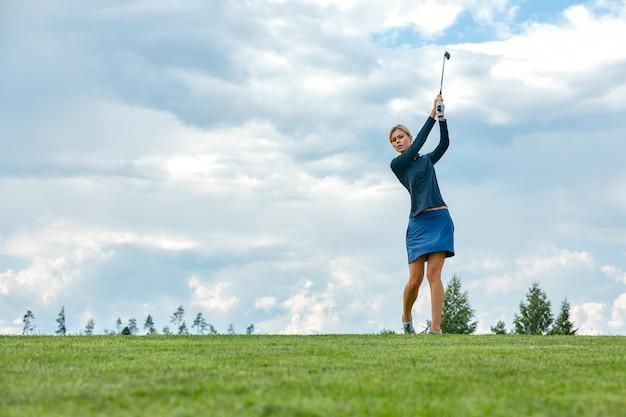 Concetto di obiettivo, copia spazio. attrezzatura da golf della tenuta di tempo golfing delle donne sul campo verde. ricerca dell'eccellenza, artigianato personale, sport reale, bandiera sportiva.
