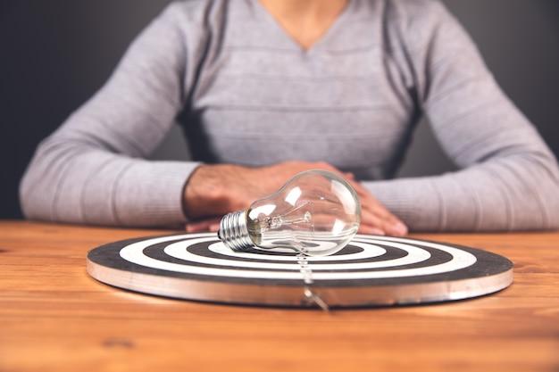 Concetto di obiettivo, l'uomo raggiunge l'obiettivo, sul tavolo, l'idea, la lampada